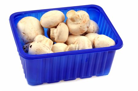 Tray of fresh and raw mushrooms in closeup on white background Stock Photo