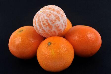 Tangerine peeled on other mandarins on a black background