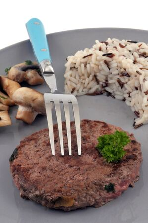 Chopped steak with rice and mushrooms served on a plate