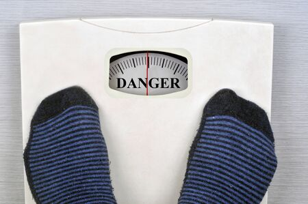 Overweight concept with scales showing danger Stock Photo