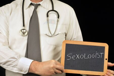 Sexologist written on school slate held in hand by a doctor