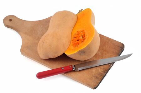 Butternut cut in half on a cutting board close up on white background Stock Photo