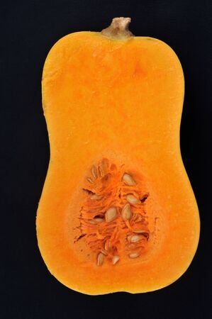 Raw butternut cut in half in close-up on black background