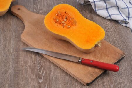 Raw butternut cut in half on a cutting board