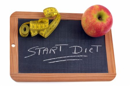 Start diet written on a school slate with an apple and a seamstress meter
