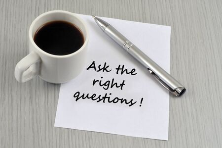 Ask the right question written on a sheet of paper near a cup of coffee