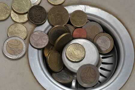 Euro coins on the drain of a sink Stock Photo