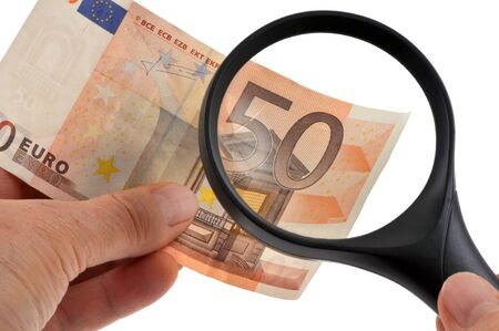 Checking a fifty euro bill with a magnifying glass