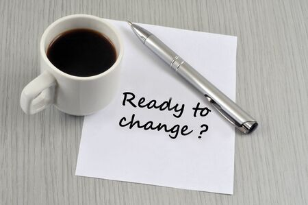 Ready to change written on a sheet of paper with a pen and a cup of coffee Banco de Imagens