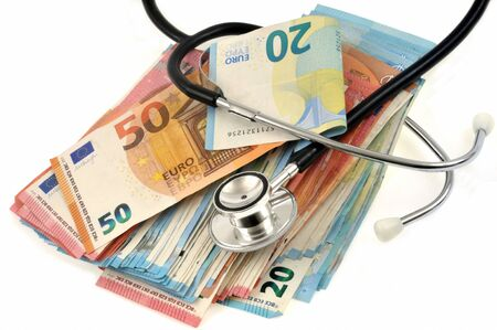 Stethoscope on euro bank notes close up on white background