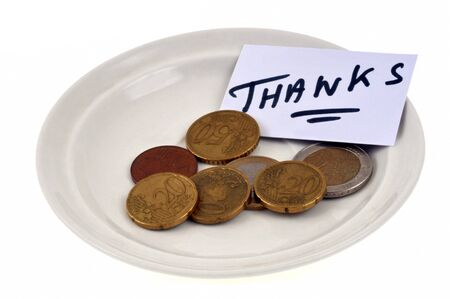 Tipping in a saucer with a card that says Thanks in close-up on a white background