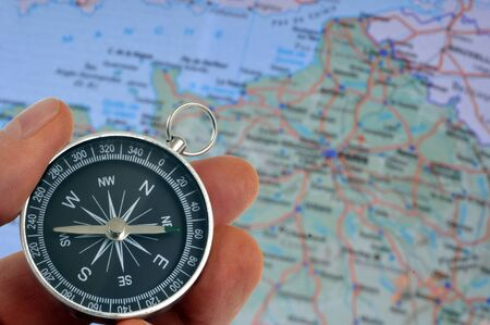 Compass in hand with a blurred map of France in the background Фото со стока