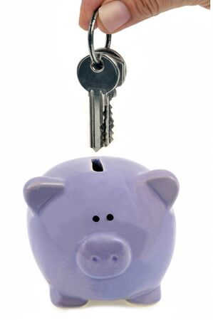Put a bunch of keys in a piggy bank close-up on a white background Stock Photo