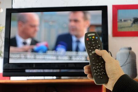 Switch TV channels with a remote control in hand