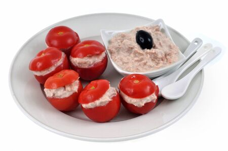 Amuse-bouche with cherry tomatoes stuffed with tuna rillettes served on a plate on white background