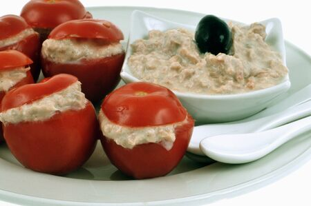 Amuse-bouche with cherry tomatoes stuffed with tuna rillettes served on a plate close-up