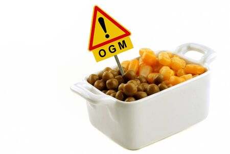 Concept of genetically modified organism with corn and peas in a ramekin with a road sign Banque d'images