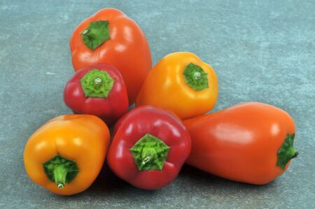 Small peppers of different colors close up on gray background Banco de Imagens