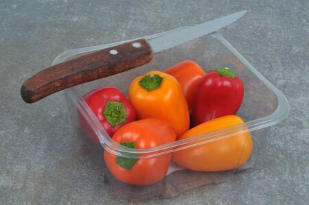 Small peppers of different colors in a plastic package with a duckling close-up on a gray background
