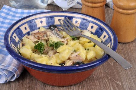 Herring and potatoes in oil close-up in a salad bowl