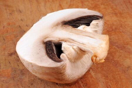 Raw mushroom cut in half o nwooden background