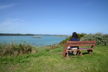 Woman sitting on bench facing the sea