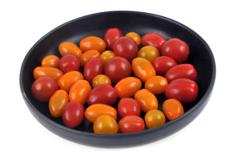 Plate of two-colored cherry tomatoes on a white background