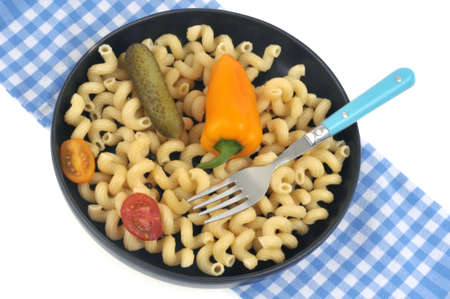Plate of pasta with vegetables close-up on white background