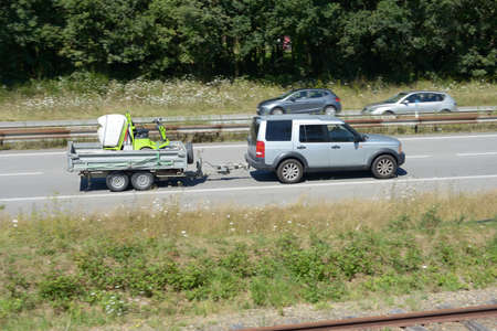Car towing a trailer with a mower on an expressway Stockfoto