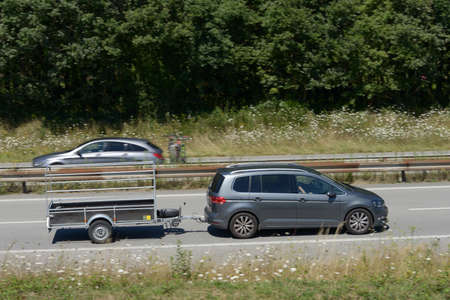 Car towing a trailer on a fast lane