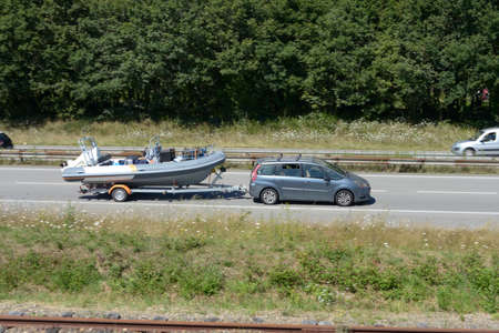 Car towing a motor boat on a trailer