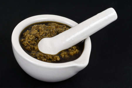 Homemade pesto in a mortar with a pestle close-up on black background