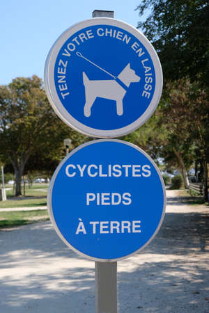 Signs indicating in French keep your dog on a leash and cyclist feet on the ground