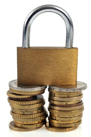Padlock on stacks of coins close up on white background