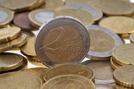 Two euro coin close-up among other coins