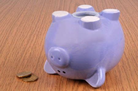 Bankruptcy concept with an overturned piggy bank and some coins Stock Photo