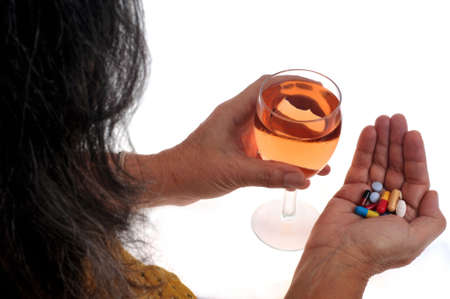 Woman with a mixture of drugs in one hand and a glass of wine in the other close-up on white background 版權商用圖片