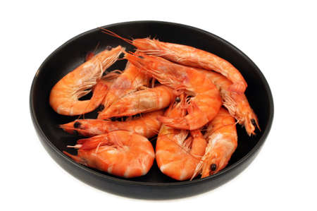 Shrimps in a black plate close-up on white background Banque d'images