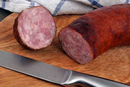 Garlic sausage cut on a cutting board with a knife Banque d'images