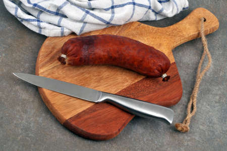 Garlic sausage on a cutting board with a knife