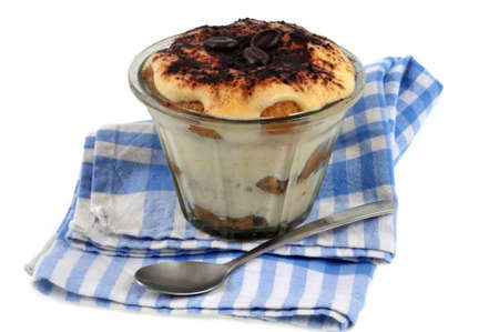Homemade tiramisu served in a ramekin placed on a napkin on a white background Banque d'images