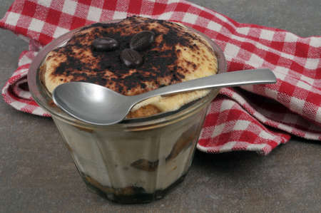 Homemade tiramisu served in a ramekin with a spoon close up Banque d'images