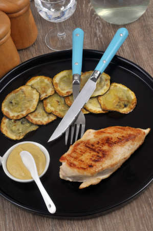 Chicken cutlet served with zucchini slices on a plate
