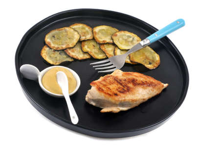 Chicken cutlet served with zucchini slices on a plate on white background Banque d'images