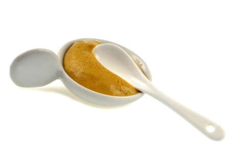 Ramekin of mustard with a spoon close-up on white background Banque d'images