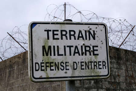 Sign indicating military land with no entry ban with barbed wire in the background
