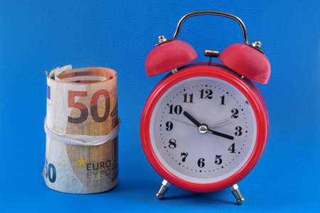 Alarm clock next to a roll of euro banknotes on a blue background