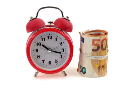 Alarm clock next to a roll of euro banknotes on a white background