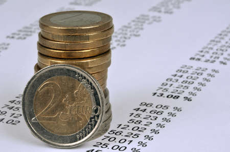 Stack of euro coins on a list of numbers close up Standard-Bild