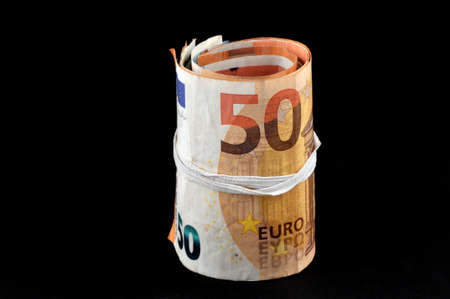 Roll of euro banknotes on black background